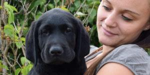 Pepsi, labrador noir chiot dans les bras de sa famille d'accueil