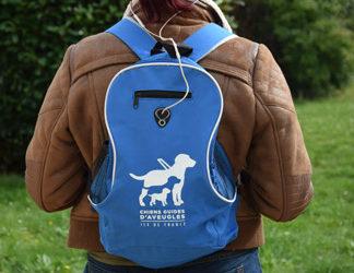 Sac à dos bleu avec logo blanc, sortie pour ecouteur, deux poches filets latérales